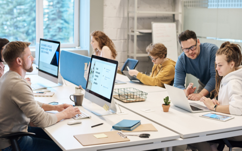 multiple people working in an office with computer screens