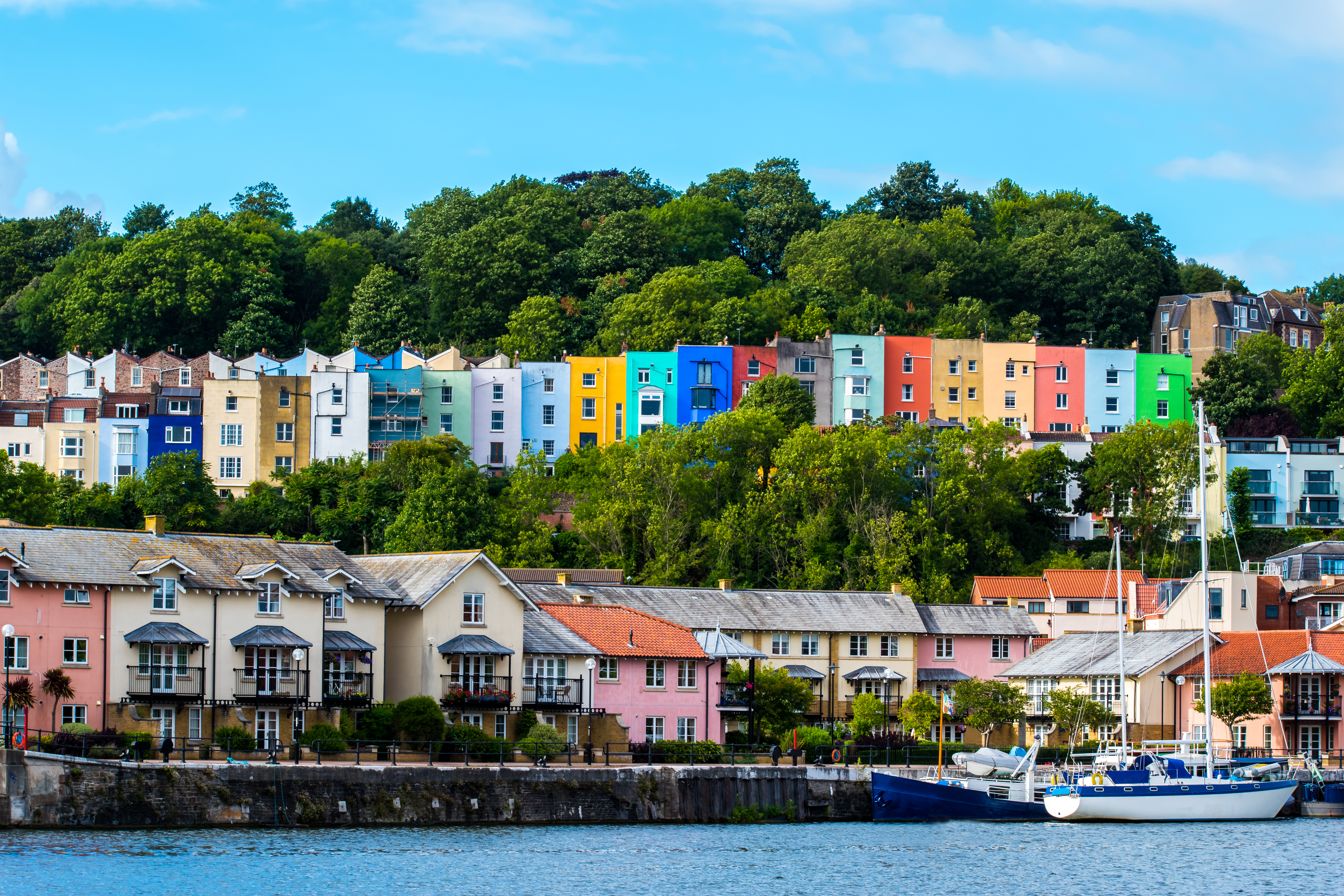 Multicoloured houses overlooking the water in Bristol with boat